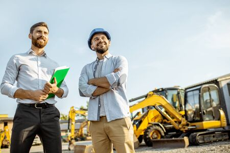 Photo pour Builder choosing heavy machinery for construction with a sales consultant standing with some documents on the open ground of a shop with special vehicles - image libre de droit