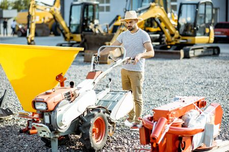 Photo pour Agronomist choosing farm cultivator machine at the outdoor ground of the shop with agricultural machinery - image libre de droit
