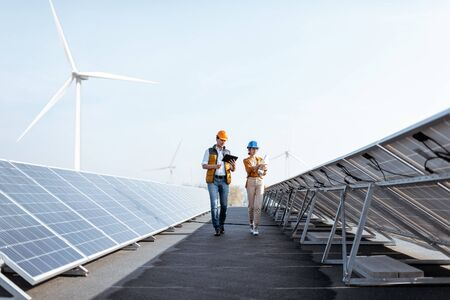 Photo pour View on the rooftop solar power plant with two engineers walking and examining photovoltaic panels. Concept of alternative energy and its service - image libre de droit