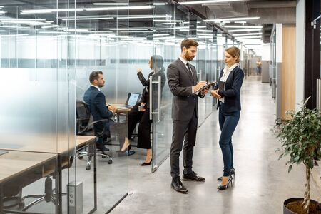 Photo for Business people talking in the hallway of the modern office building with employees working behind glass partitions. Work in a large business corporation - Royalty Free Image