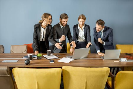 Photo for White-collar employees feeling happy and escited, having profitable deal, standing together in the colorful meeting room - Royalty Free Image