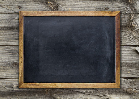 Photo pour Front view of a blank blackboard over a weathered wooden surface - image libre de droit