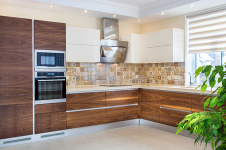 Photo pour Modern home interior. Modern design of the kitchen in a light, bright interior. Kitchen wood facades are made from walnut veneer. European furniture, design, technologies. - image libre de droit