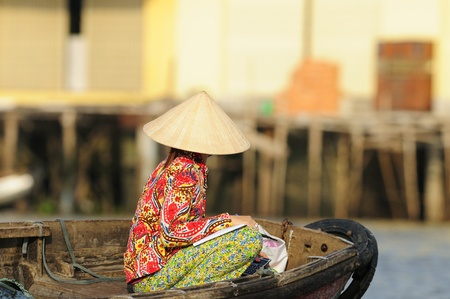 Photo for A Vietnamese Lady Sitting on a Boat at a Morning Market in the Mekong Delta - Royalty Free Image