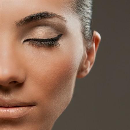 Closeup shot of half beautiful female model face with professional fashion makeup