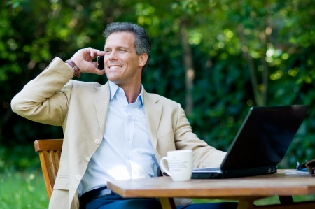 Healthy mature businessman working outdoor with mobile and laptop