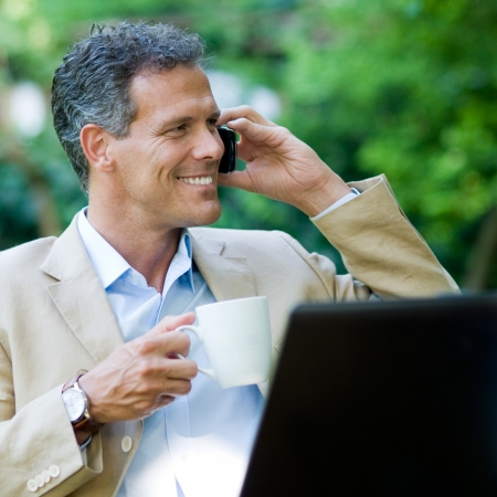 Healthy mature businessman working outdoor with mobile and laptop while drinking a mug of coffee