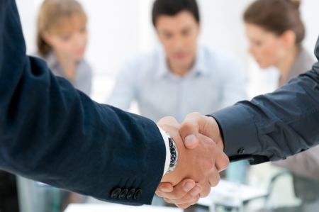 Business men shaking hands after an agreement during a meeting