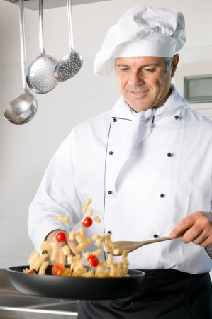 Happy mature chef stir-fry Italian pasta on a cooking pan at restaurant