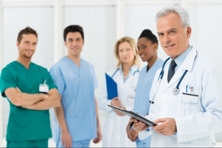 Photo for Portrait Of A Doctor and his colleagues With Medical Records - Royalty Free Image