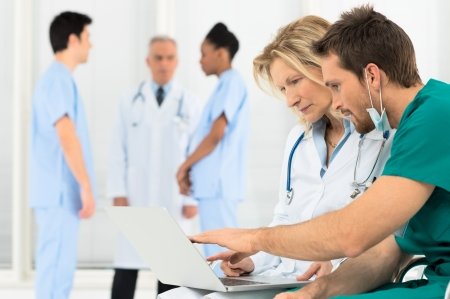 Photo for Group Of Doctors Working On Laptop In Hospital - Royalty Free Image