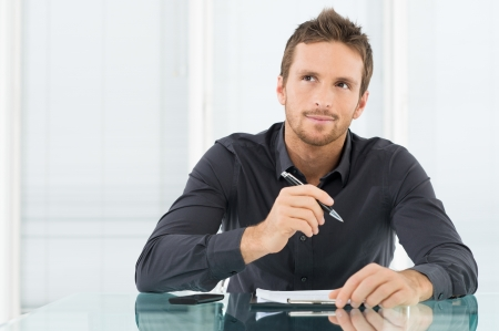 Photo for Young Businessman Thinking and Wondering While Writing a Paper - Royalty Free Image