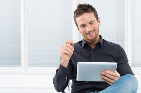 Photo for Portrait Of A Handsome Young Happy Man Using Digital Tablet - Royalty Free Image