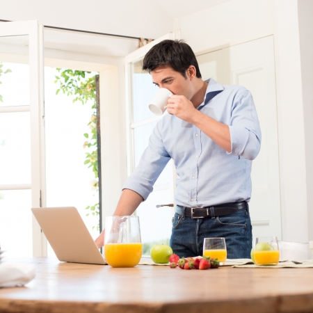 Photo for Portrait Of Young Man Using Laptop While Having Breakfast - Royalty Free Image