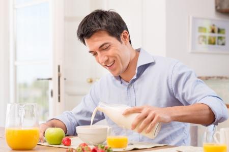 Photo pour Happy Young Man Pouring Milk Into Bowl For Breakfast - image libre de droit