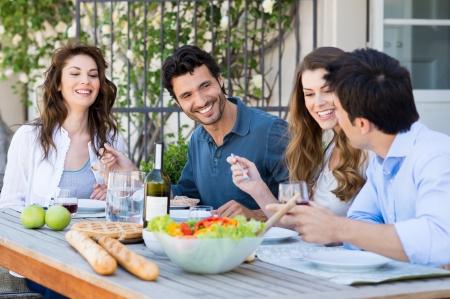 Foto de Group Of Happy Friends Having Dinner At Patio - Imagen libre de derechos