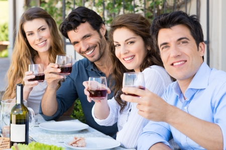 Portrait Of Happy Young Group Friends Holding Wine Glass Outdoor