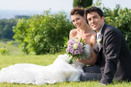 Foto per Portrait Of Happy Married Young Couple Sitting on Grass - Immagine Royalty Free