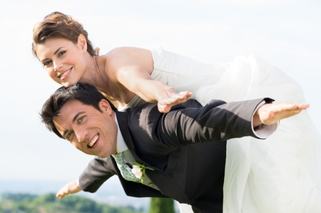 Photo pour Happy Groom Giving Piggyback Ride To His Bride at Wedding - image libre de droit
