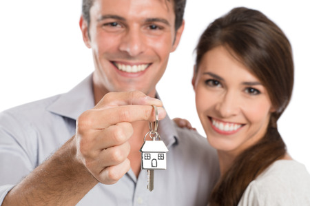 Foto de Happy Smiling Young Couple Showing Key Of Their New House Isolated On White Background - Imagen libre de derechos