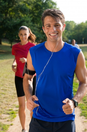 Photo pour Young Man Listening Music On Earphone With Young Woman - image libre de droit