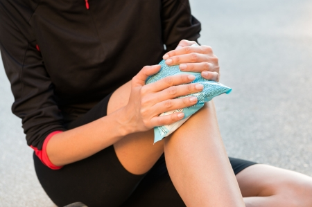 Photo pour Female Athlete Sitting On Ground And Taking Treatment For Knee Pain - image libre de droit