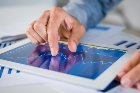 Foto de Close Up Of Businessman's Hand Analysing Graph On Digital Tablet - Imagen libre de derechos