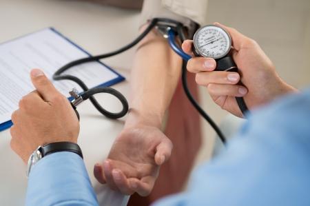 Foto de Close Up Of A Doctor Checking Blood Pressure Of A Patient - Imagen libre de derechos