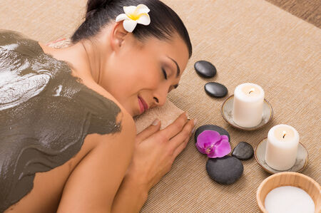 Photo pour Relaxed Woman Receiving A Mud Treatment At Spa - image libre de droit