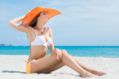 Photo for Beautiful Attractive Woman In Bikini Sitting At Beach With Sun Protection Cream - Royalty Free Image