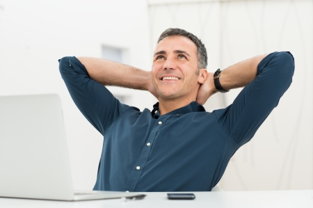 Foto de Mature Man Satisfied Sitting In Front Of Laptop Daydreaming - Imagen libre de derechos