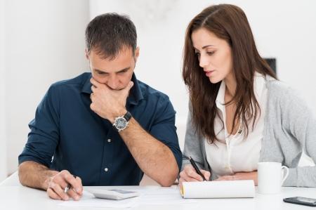 Foto de Portrait Of A Worried Couple Calculating Financial Budget - Imagen libre de derechos