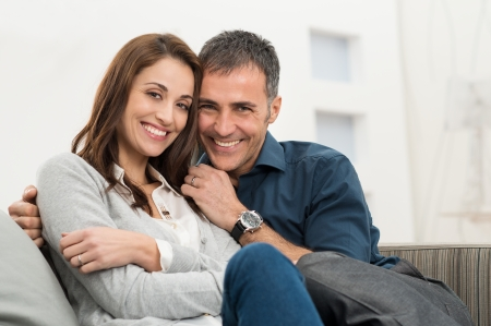 Photo pour Happy Couple Embracing Sitting On Couch Looking At Camera - image libre de droit