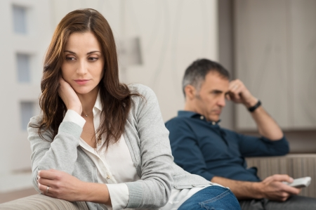 Photo pour Sad Couple Sitting On Couch After Having Quarrel - image libre de droit