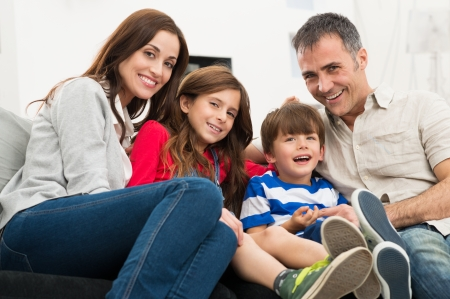 Photo pour Portrait Of A Happy Smiling Family Sitting On Couch - image libre de droit