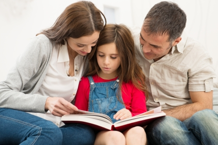 Photo pour Mother And Father Helping Their Daughter While Reading Book - image libre de droit
