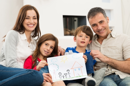 Photo pour Smiling Parents With Children Sitting On Couch Showing Together Drawing of a new Home - image libre de droit