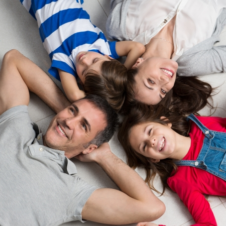 Photo for High Angle View Of Happy Family With Two Children Lying On Floor - Royalty Free Image