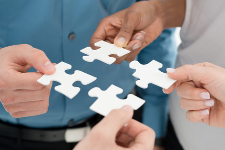 Foto de Closeup Businesspeople Hand Holding Jigsaw Puzzle - Imagen libre de derechos