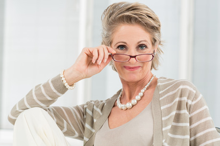 Foto de Portrait Of Happy Mature Woman Looking Through Glasses - Imagen libre de derechos