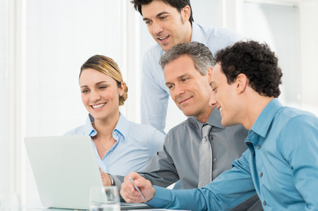 Photo pour Group Of Happy Businesspeople In Office Looking At Laptop - image libre de droit