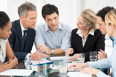 Foto de Portrait Of Multiracial Businesspeople Brainstorming In Meeting - Imagen libre de derechos