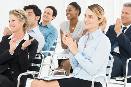 Foto de Group Of Happy Multiracial Businesspeople Clapping At Seminar - Imagen libre de derechos