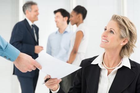 Photo pour Portrait Of Smiling Mature Businessman Giving Document To Colleague - image libre de droit