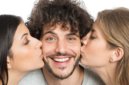 Photo pour Closeup Of Two Young Women Kissing Handsome Man - image libre de droit