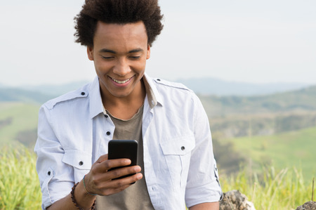 Photo for Young African Man Looking At Mobile Phone - Royalty Free Image