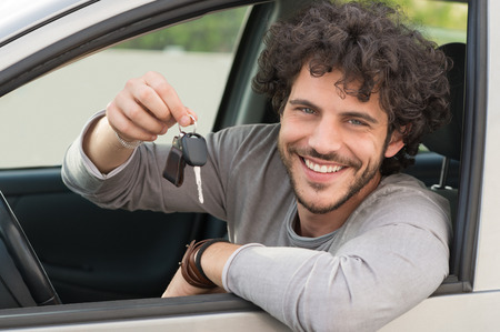 Photo for Portrait Of Young Happy Man Showing The Key Sitting In New Car - Royalty Free Image