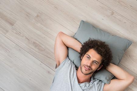 Foto de High Angle View Of Young Man Lying On Floor Thinking - Imagen libre de derechos
