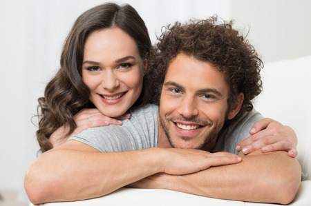 Photo pour Portrait Of Smiling Loving Young Couple Lying On Couch - image libre de droit