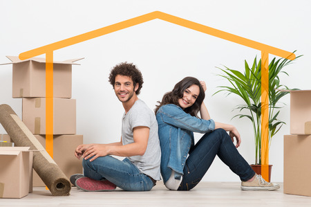 Photo pour Smiling Young Couple Sitting Back To Back After Moving House - image libre de droit
